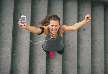 Portrait of happy fitness young woman with cell phone