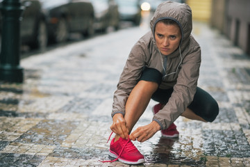 Fitness young woman tying shoelaces in rainy city