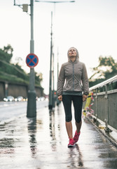 Portrait of fitness young woman walking in rainy city