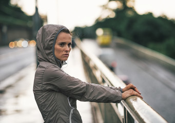 Portrait of fitness woman looking into distance in rainy city