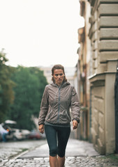 Fitness young woman walking outdoors in rainy city