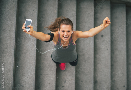 Leinwanddruck Bild Portrait of happy fitness young woman with cell phone
