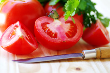 ripe tomato sliced  and knife on table