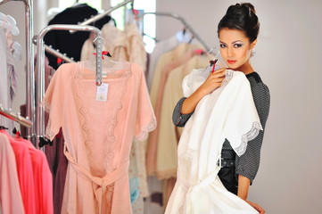 Woman shopping for dress in clothing retail store