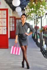 Beautiful female model with shopping bag. Full length portrait
