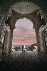 Wedding kiss under arch of the palace.