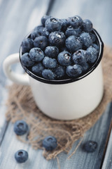 Enameled cup with ripe blueberries, close-up
