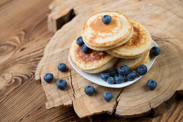 Pancakes with blueberries, rustic wooden background, studio shot