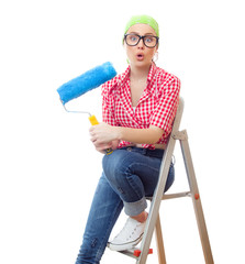Amazed woman with roller ready for wall painting