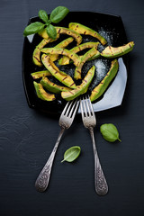 Glass plate with grilled avocado, sea salt and basil on black