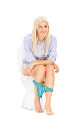 Blond girl peeing seated on a toilet