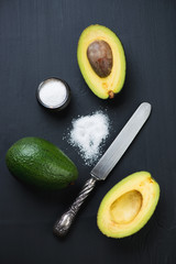 Sliced and whole avocado with sea salt on black, view from above