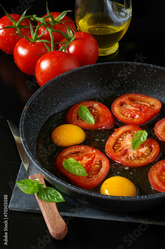 Tasty breakfast : fried eggs with tomatoes, cooking - 70303588