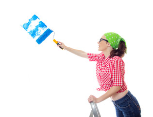 Happy woman painting a wall an blue color