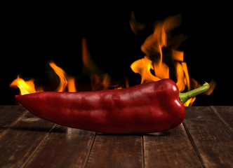 Red Hot Pepper on Wooden Table with Flames on background