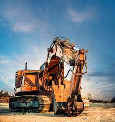 old digger at sunset horizon ground