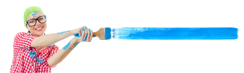 Smiling woman painting a wall an blue color