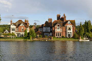 old houses and a white canoe over river Thames, Marlow