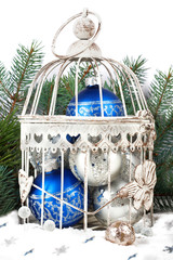 Blue and silver christmas balls in cage on the background of fir