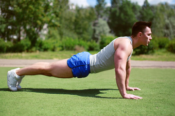 Fitness, workout, sport - concept. Sportsman push ups outdoors
