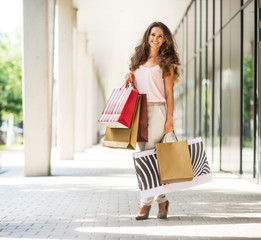 Full length portrait of smiling young woman with shopping bags