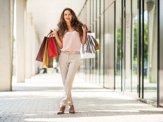 Full length portrait of happy young woman with shopping bags