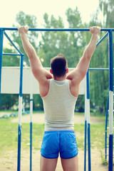 Workout sports man pull up on the horizontal bar