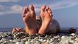 Feet / heels of a girl sunbathing at the pebble sea beach.