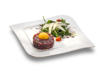 Delicious Steak tartar with yolk and rocket salad ready to serve