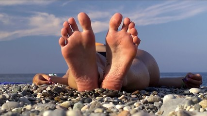 Feet / heels of a girl sunbathing at the pebble sea beach.