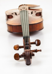 Fine violin lying on a white surface with scroll at fore