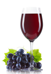 Glass of red wine with bottle and ripe grapes isolated