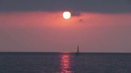 Pink sea sunset with a sailboat on the skyline.