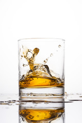 Whisky splashing in glass on a white background