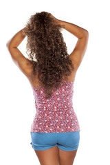 back view of young woman with curly hair on white background