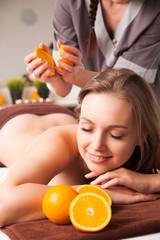 woman receiving procedures with oranges in spa