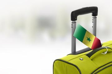 Destination Senegal. Green suitcase with flag.