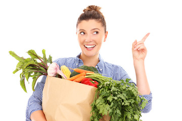 Happy woman with vegetables pointing at something