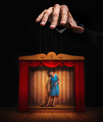 Male hand controlling a small woman puppet