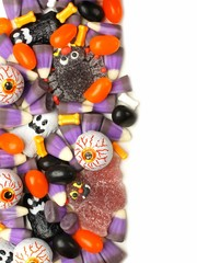 Vertical Halloween candy border over a white background