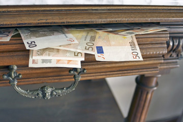 Billetes saliendo de un cajón