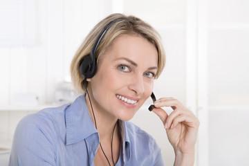 Attraktive ältere Geschäftsfrau beim Telefonieren im Büro