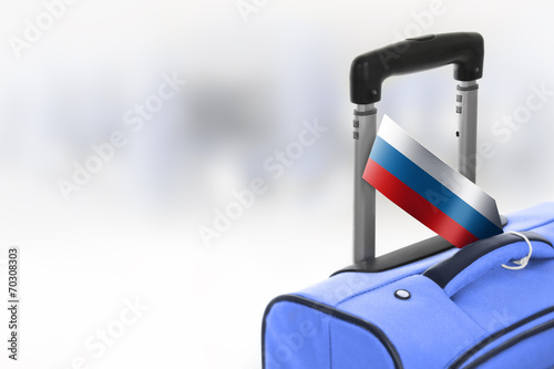 canvas print picture Destination Russia. Blue suitcase with flag.