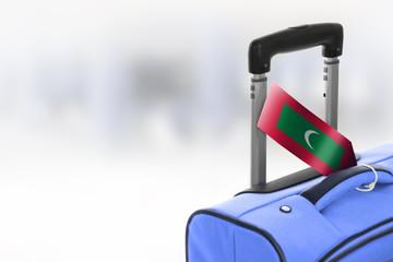 Destination Maldives. Blue suitcase with flag.
