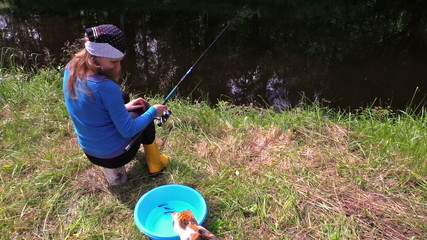 woman sit on stump near pond, watch playing cat with small fish
