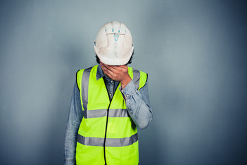 Engineer in high vis covering face