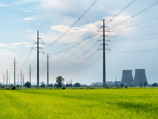 High voltage power lines. In foreground green fields, in backgro