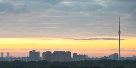 panorama of city under grey clouds at sunrise