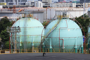 gas storage tank in oil refinery industry site with urban scen b