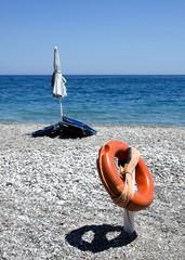 lifebuoy closed beach umbrella and beach chairs on a stony beach